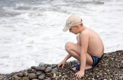 Jogo do menino com seixos Imagens de Stock Royalty Free
