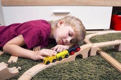 Jogo do menino da criança com trem de madeira, estrada de ferro do brinquedo da construção em casa ou Fotografia de Stock