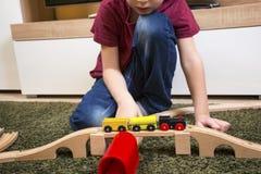 Jogo do menino da criança com trem de madeira, estrada de ferro do brinquedo da construção em casa ou Imagem de Stock