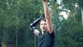 Jogo do movimento lento de um basquetebol por um adolescente com uma mão biônico robótico