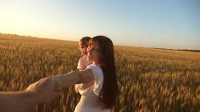Jogo do paizinho e da filha da mãe que guarda as mãos mãe e criança dos trabalhos de equipe que andam no campo, guardando seu hom vídeos de arquivo