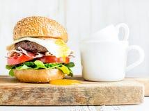 Jogo do pequeno almoço Hamburguer caseiro da carne com ovo frito, vegetais, anéis de cebola e copos de café na placa de madeira fotografia de stock royalty free