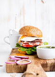 Jogo do pequeno almoço Hamburguer caseiro da carne com ovo frito, vegetais, anéis de cebola e copos de café na placa de madeira imagem de stock royalty free