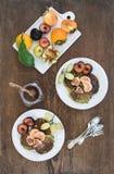Jogo do pequeno almoço Panquecas caseiros do zuccini com ameixa, a tangerina, as uvas, os figos e mel frescos nas placas cerâmica Imagens de Stock Royalty Free