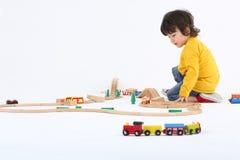 Jogo do rapaz pequeno com trens do brinquedo e a estrada de ferro de madeira grande Imagens de Stock Royalty Free
