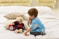 Jogo do rapaz pequeno em casa Infância feliz Dia surpreendente Cuidado e desenvolvimento Rapaz pequeno que joga com urso Família  imagem de stock royalty free