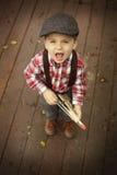 Jogo do rapaz pequeno exterior com uma arma de madeira do brinquedo imagens de stock
