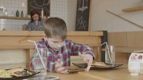 Jogo do rapaz pequeno no telefone ao comer no café filme