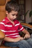 Jogo do smartphone do jogo do rapaz pequeno Foto de Stock Royalty Free