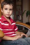Jogo do smartphone do jogo do rapaz pequeno Imagem de Stock