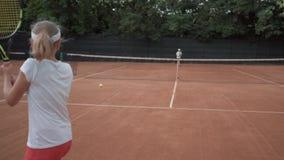 Jogo do tênis, menina adolescente do jogador dos esportes com o concorrente que bate a raquete na passagem da bola através da red filme