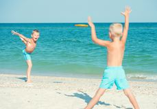 Jogo dos irmãos com o frisbee na praia Férias de verão fotografia de stock royalty free