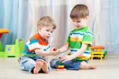 Jogo dos irmãos das crianças junto no berçário Fotos de Stock Royalty Free