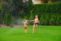 Jogo dos meninos na grama Foto de Stock