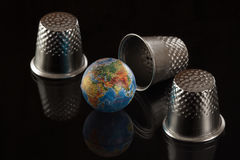 Jogo em um dedal com o globo Imagens de Stock Royalty Free
