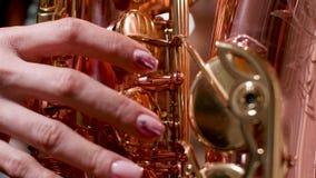 Jogo fêmea em um saxofone bonito vídeos de arquivo