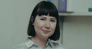 Jogo fêmea novo com emoção na frente da câmera em sua mesa do trabalho do escritório filme