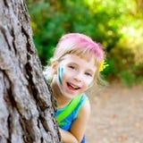 Jogo feliz da menina das crianças na árvore de floresta Fotografia de Stock