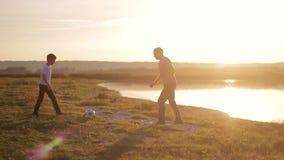 Jogo feliz do paizinho e do filho com uma bola de futebol no por do sol filme