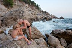 Jogo feliz dos miúdos junto em rochas do mar Foto de Stock Royalty Free