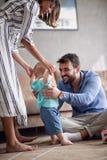 Jogo feliz e bebê da família que aprendem andar em casa fotografia de stock