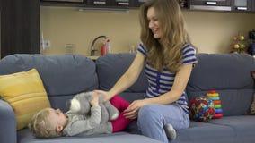 Jogo feliz novo da mãe com o bebê no sofá com brinquedo 4K filme