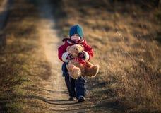 Jogo feliz novo do menino exterior com o brinquedo do urso de peluche fotos de stock royalty free