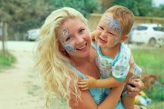 Jogo feliz pintado face da matriz e da criança Fotografia de Stock Royalty Free