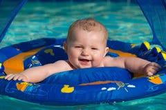 Jogo infantil feliz na associação ao sentar-se no flutuador do bebê imagens de stock