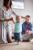 Jogo novo feliz e bebê da família que aprendem andar em casa imagem de stock
