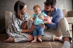 Jogo orgulhoso novo e bebê da família que aprendem andar em casa imagem de stock