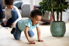 Jogo preto pequeno engraçado da criança com carro do brinquedo imagem de stock royalty free