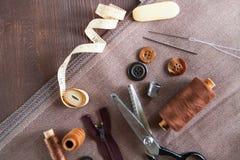 jogo Scissor, botões, fecho de correr, fita métrica, linha e dedal sobre fotografia de stock royalty free
