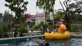 Jogo tailandês asiático da mulher e borracha animal nadadora do brinquedo que flutuam na água da associação filme