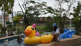 Jogo tailandês asiático da mulher e borracha animal nadadora do brinquedo que flutuam na associação filme