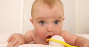 Jogo velho do bebê de quatro meses com brinquedo brilhante filme