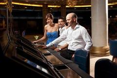 Jogo vestido formal dos adultos felizes no casino Imagens de Stock