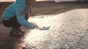 Jogos bonitos da menina com o navio de papel em um lago no tempo do por do sol Sonho da criança e conceito do curso, estilo de vi filme