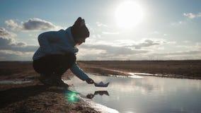 Jogos bonitos da menina com o navio de papel em um lago no tempo do por do sol Sonho da criança e conceito do curso, estilo de vi vídeos de arquivo
