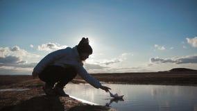 Jogos bonitos da menina com o navio de papel em um lago no tempo do por do sol Sonho da crian?a e conceito do curso, estilo de vi vídeos de arquivo