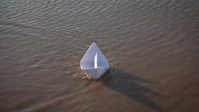 Jogos bonitos da menina com o navio de papel em um lago no tempo do por do sol Sonho da crian?a e conceito do curso, estilo de vi video estoque