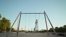 Jogos bonitos da menina em balanços no parque filme