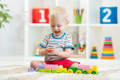 Jogos bonitos do menino com os brinquedos dos blocos de apartamentos no berçário fotos de stock royalty free