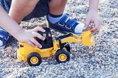 Jogos da criança com máquina escavadora do brinquedo Fotografia de Stock Royalty Free