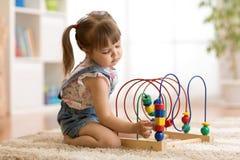 Jogos da menina da criança com brinquedo educacional dentro foto de stock royalty free