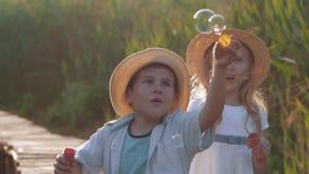 Jogos das crianças, rapaz pequeno bonito engraçado com a amiga em chapéus de palha para fundir bolhas e rir no ar livre video estoque