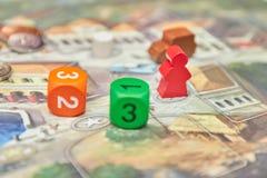 Jogos de mesa temáticos Figuras coloridas do jogo com dados a bordo ideia vertical do close-up do jogo de mesa imagens de stock royalty free