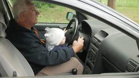 Jogos de primeira geração com o menino no carro ao conduzir O neto está muito feliz e torce os botões diferentes filme