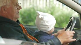 Jogos de primeira geração com o menino no carro ao conduzir O neto está muito feliz e torce os botões diferentes vídeos de arquivo