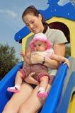 Jogos do bebé com o Mum no campo de jogos Fotografia de Stock Royalty Free